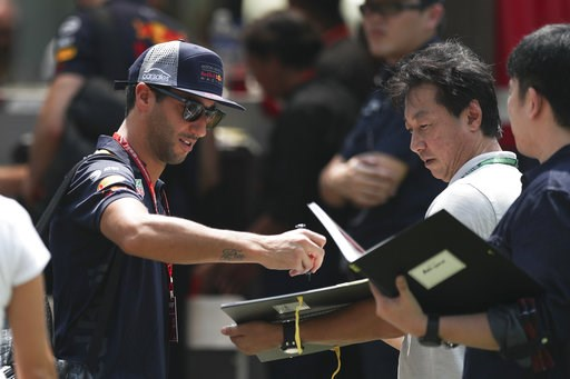 (AP Photo/Yong Teck Lim). Red Bull Racing driver Daniel Ricciardo of Australia, left, sign autograph as he arrives at the Marina Bay City Circuit ahead of the Singapore Formula One Grand Prix in Singapore, Friday, Sept. 14, 2018.
