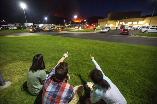 (Qiling Wang/The Deseret News via AP). In this Thursday, Sept. 13, 2018, photo, residents watch a wildfire burning from outside Salem Hills High School in Salem, Utah.