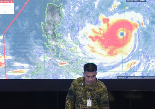 (AP Photo/Aaron Favila). A member of the Philippine Air Force stands in front of a satellite image of Typhoon Mangkhut, locally named Typhoon Ompong, at the National Disaster Risk Reduction and Management Council operations center in metropolitan Manil...