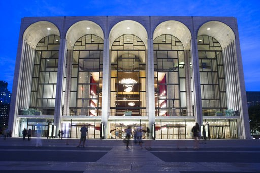 (AP Poto/John Minchillo, File). FILE - In this Aug. 1, 2014, file photo, pedestrians make their way in front of the Metropolitan Opera house at New York's Lincoln Center. The Metropolitan Opera will start regular Sunday afternoon performances for the f...