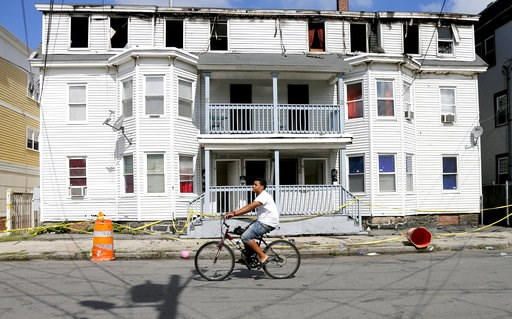(AP Photo/Mary Schwalm). A man on a bicycle rides past a house destroyed by fire on Springfield St in Lawrence, Mass., Friday, Sept. 14, 2018. Multiple houses were damaged Thursday afternoon from gas explosions and fires triggered by a problem with a g...