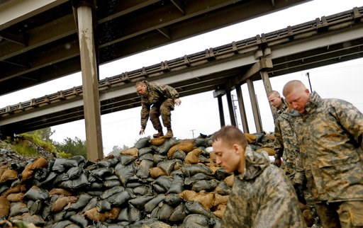 (AP Photo/David Goldman). Members of the North Carolina National Guard finish stacking sand bags under a highway overpass near the Lumber River which is expected to flood from Hurricane Florence's rain in Lumberton, N.C., Friday, Sept. 14, 2018.