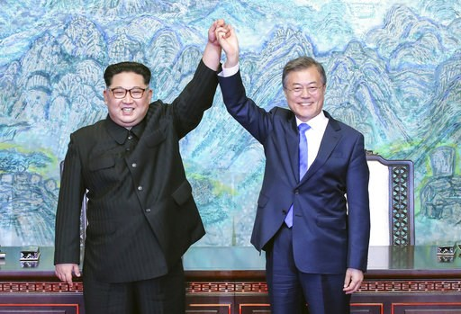 (Korea Summit Press Pool via AP, File). FILE - In this April 27, 2018 file photo, North Korean leader Kim Jong Un, left, and South Korean President Moon Jae-in raise their hands after signing a joint statement at the border village of Panmunjom in the ...