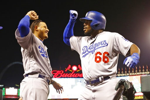 (AP Photo/Billy Hurst). Los Angeles Dodgers right fielder Yasiel Puig, right, is congratulated by teammate Manny Machado after hitting a home run during the first inning of a baseball game against the St. Louis Cardinals Friday, Sept. 14, 2018, in St. ...
