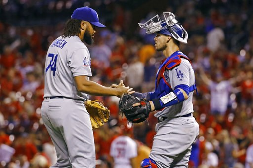 (AP Photo/Billy Hurst). Los Angeles Dodgers relief pitcher Kenley Jansen and catcher Yasmani Grandal, right, shake hands after the last out in the ninth inning of a baseball game against the St. Louis Cardinals, Friday, Sept. 14, 2018, in St. Louis. Th...
