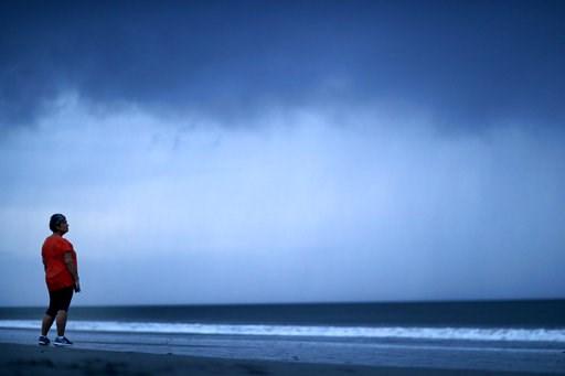 (AP Photo/David Goldman). Paula Thibodeau, of Conway, S.C., watches a storm cloud as Hurricane Florence approaches Myrtle Beach, S.C., Thursday, Sept. 13, 2018.