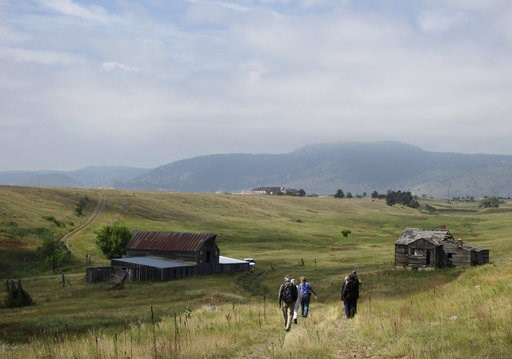 (AP Photo/Dan Elliott, File). FILE - In this Aug. 11, 2017 file photo, visitors approach a former ranch house and barn during a guided hike on the Rocky Flats National Wildlife Refuge near Denver. The U.S. Interior Department says it will go ahead with...