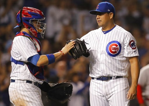 (AP Photo/Jim Young). Chicago Cubs' Jorge De La Rosa, right, and Victor Caratini celebrate their win over the Cincinnati Reds at the end of a baseball game Friday, Sept. 14, 2018, in Chicago.