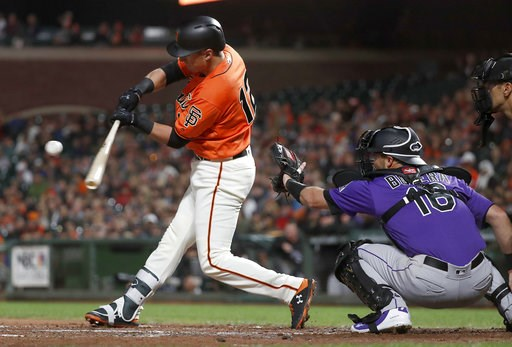 (AP Photo/Tony Avelar). San Francisco Giants' Joe Panik (12) hits a single against the Colorado Rockies during the second inning of a baseball game in San Francisco, Friday, Sept. 14, 2018.