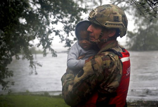 (AP Photo/Chris Seward). Rescue team member Sgt. Nick Muhar, from the North Carolina National Guard 1/120th battalion, evacuates a young child as the rising floodwaters from Hurricane Florence threatens his home in New Bern, N.C., on Friday, Sept. 14, ...