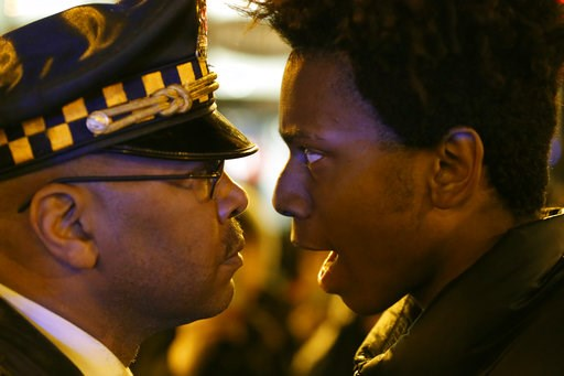 "(AP Photo/Charles Rex Arbogast). FILE - In this Wednesday, Nov. 25, 2015 file photo, Lamon Reccord, right, stares and yells, ""Shoot me 16 times,"" at a Chicago police officer as he and others march through Chicago's Loop, one day after murder charges we..."