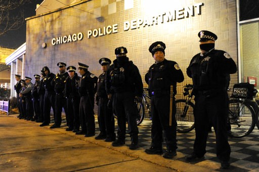 (AP Photo/Paul Beaty). FILE - In this Tuesday, Nov. 24, 2015 file photo, police officers line up outside the District 1 central headquarters at 17th and State streets in Chicago, during a protest for 17-year-old Laquan McDonald, who was fatally shot in...