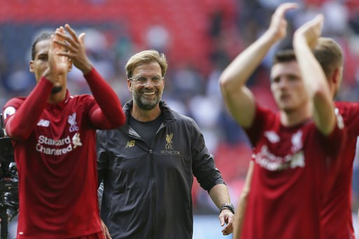 (AP Photo/Tim Ireland). Liverpool's coach Jurgen Klopp center, celebrates with Liverpool's players after winning the English Premier League soccer match between Tottenham Hotspur and Liverpool at Wembley Stadium in London, Saturday Sept. 15, 2018.