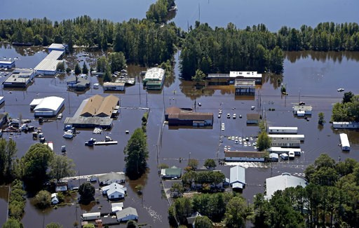(AP Photo/Chuck Burton, File). FILE - In this Oct. 12, 2016, file photo, homes and businesses are surrounded by floodwaters from Hurricane Matthew in Lumberton, N.C. The rural town, battered by the collapse of its blue-collar economy and then by Matthe...