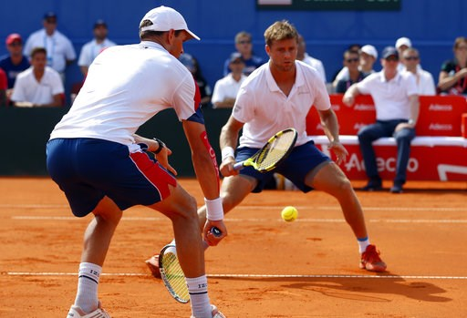 (AP Photo/Darko Bandic). Mike Bryan, left, of the US returns a shot to Ivan Dodig and Mate Pavic during the Davis Cup semifinal double match between Croatia and the United States in Zadar, Croatia, Saturday, Sept. 15, 2018.