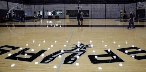 (AP Photo/Eric Gay). Former San Antonio Spurs guard Manu Ginobili, center right, walks with Spurs director of communications Tom James, center left, after talking to the media at the NBA basketball team's practice facility, Saturday, Sept. 15, 2018, in...