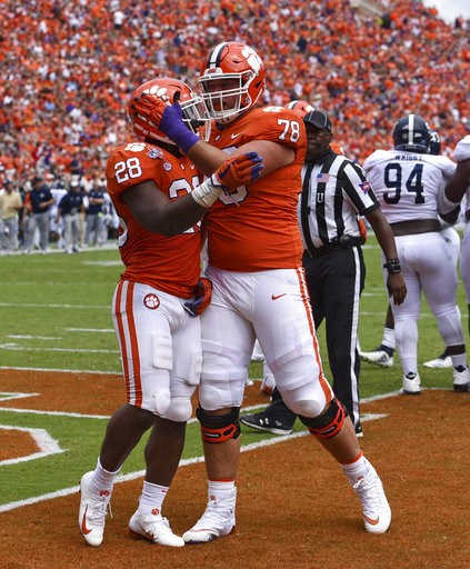 (AP Photo/Richard Shiro). Clemson's Tavien Feaster (28) celebrates his touchdown with Chandler Reeves during the first half of an NCAA college football game against Georgia Southern, Saturday, Sept. 15, 2018, in Clemson, S.C.