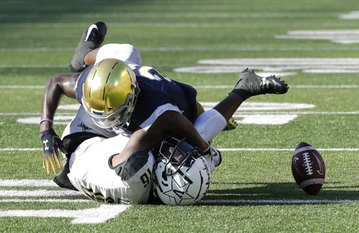 (AP Photo/Nam Y. Huh). Notre Dame safety Jalen Elliott, top, tackles as Vanderbilt wide receiver Kalija Lipscomb misses the ball during the second half of an NCAA college football game in South Bend, Ind., Saturday, Sept. 15, 2018. Notre Dame won 22-17.