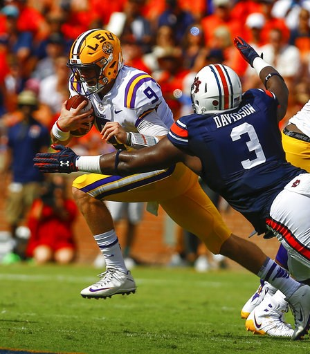 (AP Photo/Butch Dill). LSU quarterback Joe Burrow (9) carries the ball past Auburn defensive lineman Marlon Davidson (3) for the first down during the first half of an NCAA college football game, Saturday, Sept. 15, 2018, in Auburn, Ala.