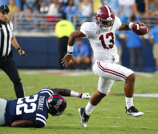 (AP Photo/Rogelio V. Solis). Alabama quarterback Tua Tagovailoa (13) evades a tackle by Mississippi defensive end Tariqious Tisdale (22) during the first half of their NCAA college football game, Saturday, Sept. 15, 2018, in Oxford, Miss.
