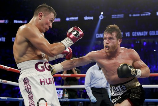 (AP Photo/Isaac Brekken). Canelo Alvarez, right, and Gennady Golovkin trade punches in the fourth round during a middleweight title boxing match, Saturday, Sept. 15, 2018, in Las Vegas.