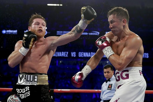 (AP Photo/Isaac Brekken). Canelo Alvarez, left, and Gennady Golovkin trade punches in the third round during a middleweight title boxing match, Saturday, Sept. 15, 2018, in Las Vegas.