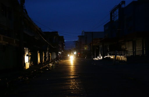 (AP Photo/Aaron Favila). A motorcycle provides light along a dark street after electricity was shut-off following the onslaught of Typhoon Mangkhut in Tuguegarao city in Cagayan province, northeastern Philippines on Saturday, Sept. 15, 2018. The typhoo...