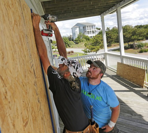 (AP Photo/Tom Copeland, File). FILE - In this Wednesday, Sept. 12, 2018 file photo, Joe Gore, left, and Joshua Adcock prepare for Hurricane Florence as they board up windows on a home in Emerald Isle N.C. Before and after a hurricane, Ace is the place....