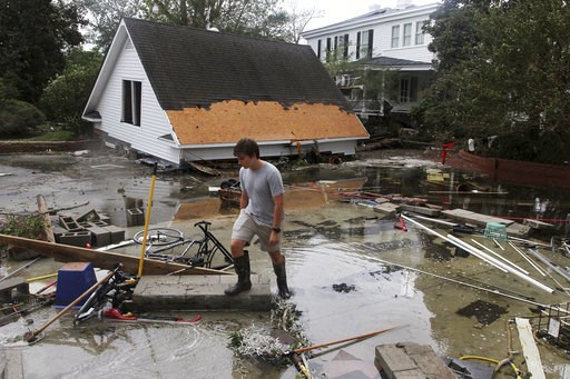(Gray Whitley/Sun Journal via AP). Resident Joseph Eudi looks at flood debris and storm damage from Hurricane Florence at a home on East Front Street in New Bern, N.C., Saturday, Sept. 15, 2018.