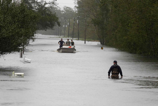 (AP Photo/Tom Copeland). A member of the US Coast Guard walks down Mill Creek Road checking houses after tropical storm Florence hit Newport N.C., Saturday, Sept. 15, 2018. A day after blowing ashore with 90 mph (145 kph) winds, Florence practically pa...