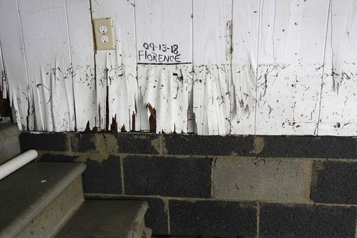 (AP Photo/Tom Copeland). A high water mark is written on the side of Lynda Willis' home after Hurricane Florence hit Davis N.C., Saturday, Sept. 15, 2018.