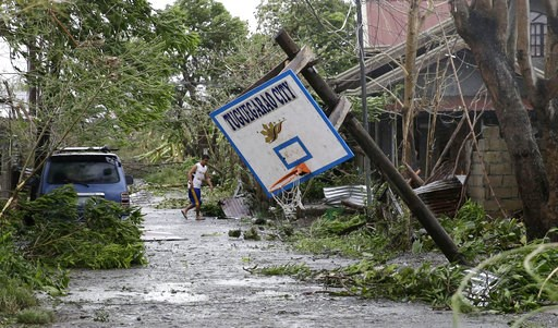 (AP Photo/Aaron Favila). A resident walks beside a toppled basketball court after Typhoon Mangkhut barreled across Tuguegarao city,  Cagayan province, northeastern Philippines, Saturday, Sept. 15, 2018. Philippine officials were assessing damage and ch...