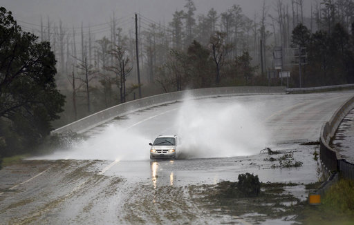 (Matt Born/The Star-News via AP). A car drives through water caused by the rain from Florence, now a tropical storm on U.S. 74/76 in Leland, N.C., Saturday, Sept.15, 2018. The rain from Hurricane Florence was expected to continue through Sunday.