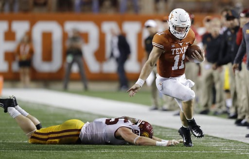 (AP Photo/Eric Gay). Texas quarterback Sam Ehlinger (11) works to stay in bounds as he runs past Southern California linebacker Porter Gustin (45) during the first half of an NCAA college football game, Saturday, Sept. 15, 2018, in Austin, Texas.