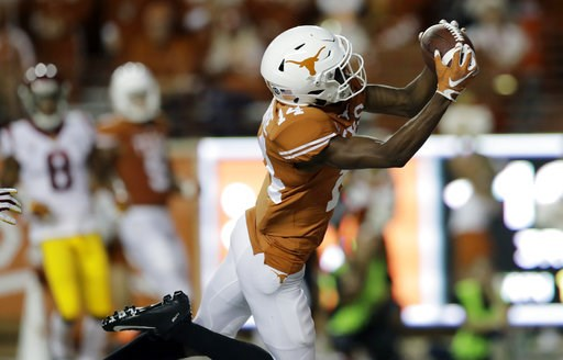 (AP Photo/Eric Gay). Texas wide receiver Joshua Moore (14) pulls in a 27-yard pass for a touchdown against Southern California during the second half of an NCAA college football game, Saturday, Sept. 15, 2018, in Austin, Texas.