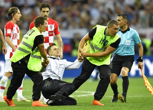 (AP Photo/Martin Meissner, File). FILE - In this July 15, 2018, stewards pull Pyotr Verzilov, a member of the feminist protest group Pussy Riot off the pitch after he stormed onto the field and interrupted the final match between France and Croatia at ...