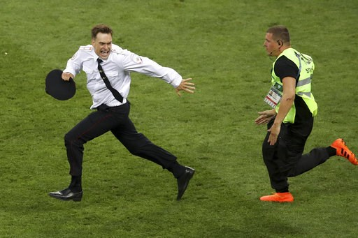 (AP Photo/Thanassis Stavrakis, File). FILE - In this Sunday, July 15, 2018 file photo, Pyotr Verzilov invading the pitch, runs away as a steward tries to stop him during the France and Croatia 2018 World Cup final match in the Luzhniki Stadium in Mosco...