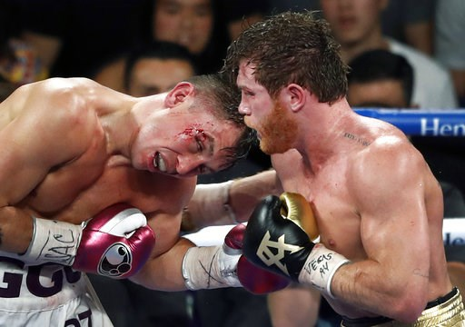 (Steve Marcus/Las Vegas Sun via AP). Canelo Alvarez, right, of Mexico, lands a punch on WBC/WBA middleweight champion Gennady Golovkin, of Khazakstan, during their title boxing fight at T-Mobile Arena in Las Vegas, Saturday, Sept. 15, 2018. Alvarez too...