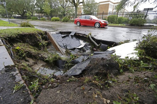 (AP Photo/Chuck Burton). A car travels past a sinkhole in downtown Wilmington, N.C., after Hurricane Florence traveled through the area Sunday, Sept. 16, 2018.