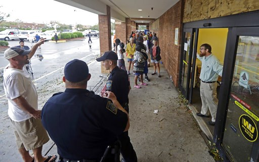 (AP Photo/Chuck Burton). Wilmington police stand guard as a Lowe's Foods employee stands by the door of the store in Wilmington, N.C., after Hurricane Florence traveled through the area Sunday, Sept. 16, 2018. The store was allowing only 10 people into...