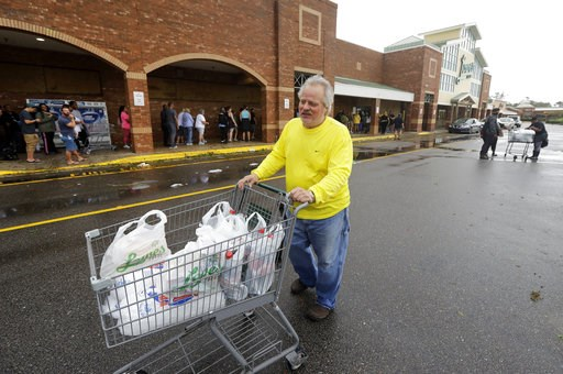 (AP Photo/Chuck Burton). Dallas Perdue leaves a Lowe's Foods store in Wilmington, N.C., after Hurricane Florence traveled through the area Sunday, Sept. 16, 2018. Perdue says he waited about two hours to get into the store to buy a few groceries. The s...
