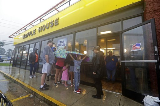 (AP Photo/Chuck Burton). Luke Churchill, left, stands with his wife, Mary and their children, Katie, 13, Liam, 9, and Raighan, 3, as they wait in the rain outside an open Waffle House restaurant in Wilmington, N.C., after Hurricane Florence traveled th...