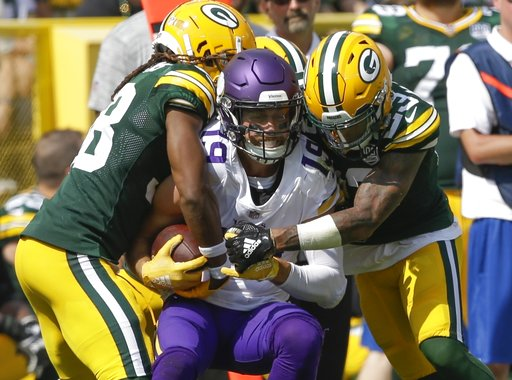 (AP Photo/Jeffrey Phelps). Minnesota Vikings' Adam Thielen catches a pass between Green Bay Packers' Tramon Williams and Jaire Alexander during the first half of an NFL football game Sunday, Sept. 16, 2018, in Green Bay, Wis.