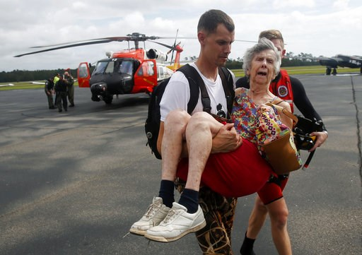 (AP Photo/Steve Helber). An unidentified family member carries Ruth Brady to safety at the Wilmington airport in Wilmington, N.C., Monday, Sept. 17, 2018. Brady was one of several family members rescued by a Coast Guard helicopter crew north of Wilming...