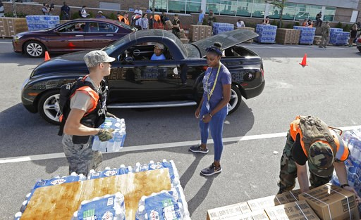 (AP Photo/Chuck Burton). Members of the Civil Air Patrol load cars with MREs, (Meals Ready To Eat) water and tarps at distribution area in Wilmington, N.C. Tuesday, Sept. 18, 2018.
