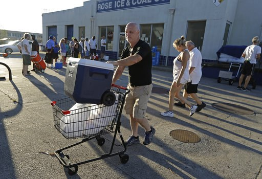 (AP Photo/Chuck Burton). Kyle Crawford uses a shopping cart to carry bags of ice he purchased days after Hurricane Florence in Wilmington, N.C. Wednesday, Sept. 19, 2018.