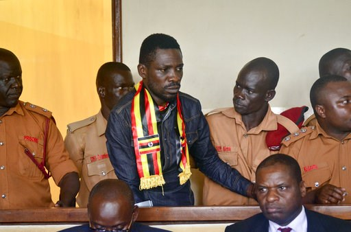 (AP Photo, File). FILE - In this Thursday, Aug. 23, 2018 file photo, Ugandan pop star-turned-lawmaker Kyagulanyi Ssentamu, also known as Bobi Wine, center, arrives at a magistrate's court in Gulu, northern Uganda. Wine is due to return home on Thursday...