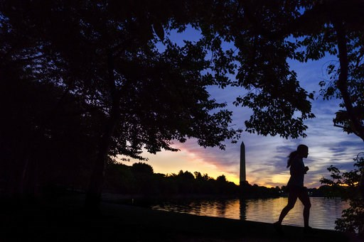 (AP Photo/J. David Ake, File). FILE - In this July 25, 2017 file photo, an early morning runner is silhouetted against the rising sun at the Tidal Basin in Washington. Recent killings of women who were attacked while engaged in the sports they love hav...