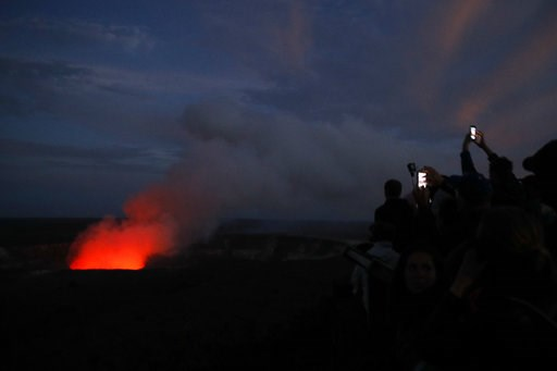 (AP Photo/Jae C. Hong, File). FILE - In this May, 9, 2018, file photo, visitors take pictures as Kilauea's summit crater glows red in Volcanoes National Park, Hawaii. The Hawaii Volcanoes National Park will reopen its main gates Saturday, Sept. 22, 201...