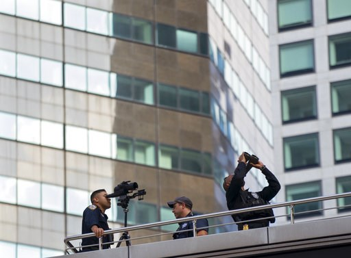 (AP Photo/Craig Ruttle). FILE- In this Sept. 17, 2017 file photo, a security team near Trump Tower looks towards high floors of nearby buildings shortly before the arrival of President Donald Trump in New York. Authorities in New York City are facing a...